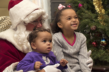 Two children smiling while sitting on Santa Claus' lap during Plymouth's Old Fashioned Christmas event