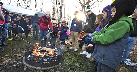 Roasting s'mores outdoors by the bon fire at Plymouth's Old Fashioned Christmas event