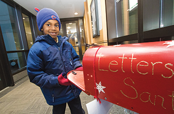 Child dropping off letter for Santa Claus at Plymouth City Hall