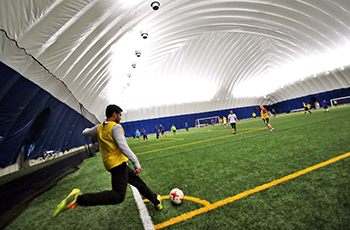 Soccer player kicking the ball inside the Plymouth Creek Center Fieldhouse dome