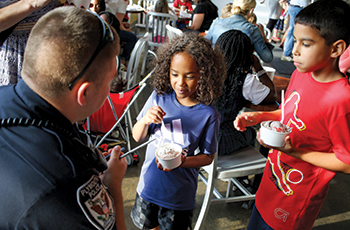 Children enjoying ice cream during the Plymouth Police Department's Cones with Cops event