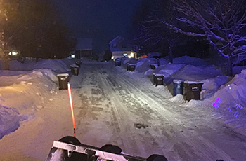 Plow drivers clearing city streets with garbage carts