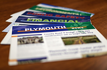 City newsletters on a table, featuring the Plymouth News