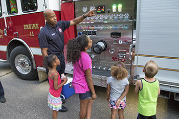 Plymouth firefighter teaching about fire trucks