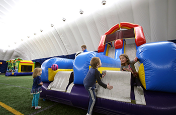 Children playing on inflatables during open play at the Plymouth Creek Center Fieldhouse dome