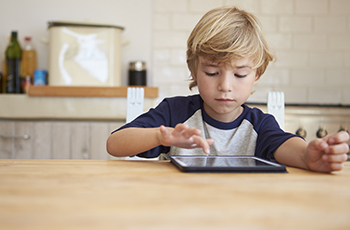 Boy home alone, playing with a mobile tablet device