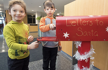 Children dropping off letters for Santa Claus in a big red mailbox at Plymouth City Hall