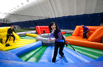 Adults on inflatables during the After Hours at the Creek event