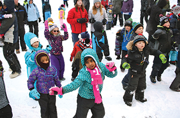 Children dancing along with music on the frozen lake during Plymouth's Fire & Ice