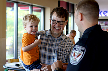 Plymouth police officer talking with a dad and son at a community engagement event