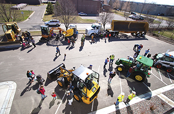 Residents exploring vehicles and equipment at the touch-a-truck portion of the City Sampler event at the Plymouth Maintenance Facility