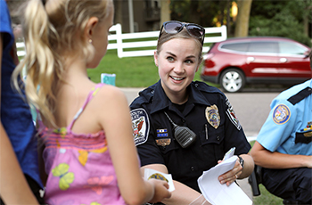 Plymouth police officer smiling and talking to a child at a neighborhood Night to Unite block party