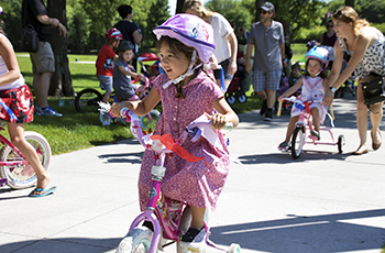 Child riding a decorated bike during the Happy Birthday America Parade